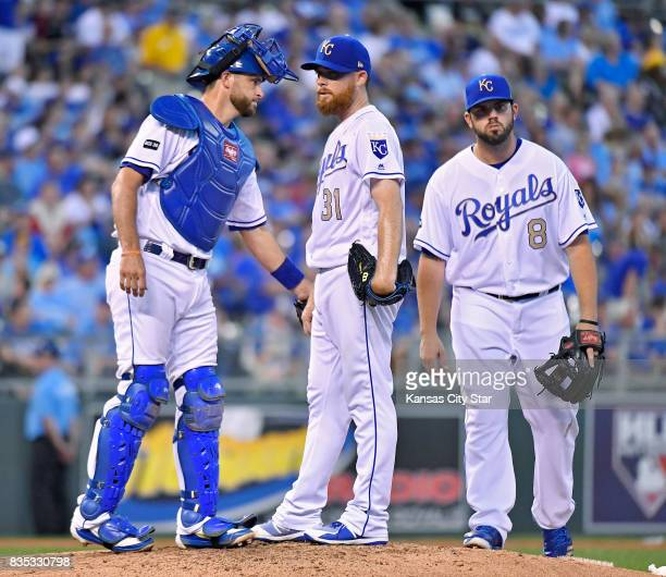 Kansas City Royals starting pitcher Ian Kennedy middle waits to be relieved while standing with catcher Drew Butera and third baseman Mike Moustakas...