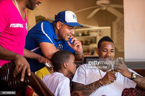 Kansas City Royals starting pitcher Yordano Ventura right shows photos on his cell phone to Victor Baez Royals Dominican Baseball Academy field...
