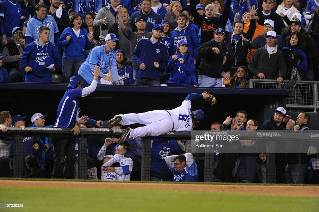 Kansas City Royals third baseman Mike Moustakas dives into dugout suites to catch a foul fly ball by the Baltimore Orioles' Adam Jones in the sixth...