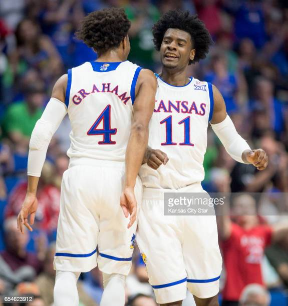 Kansas' Devonte' Graham and Josh Jackson celebrate after Jackson put the Jayhawks up by 10 in the first half against UC Davis during the first round...