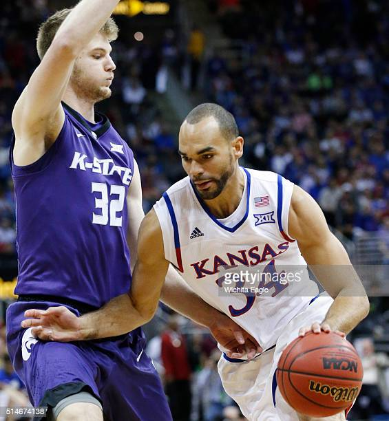 Kansas forward Perry Ellis drives past Kansas State forward Dean Wade on his way to the basket during the quarterfinal round of the Big 12 Men's...