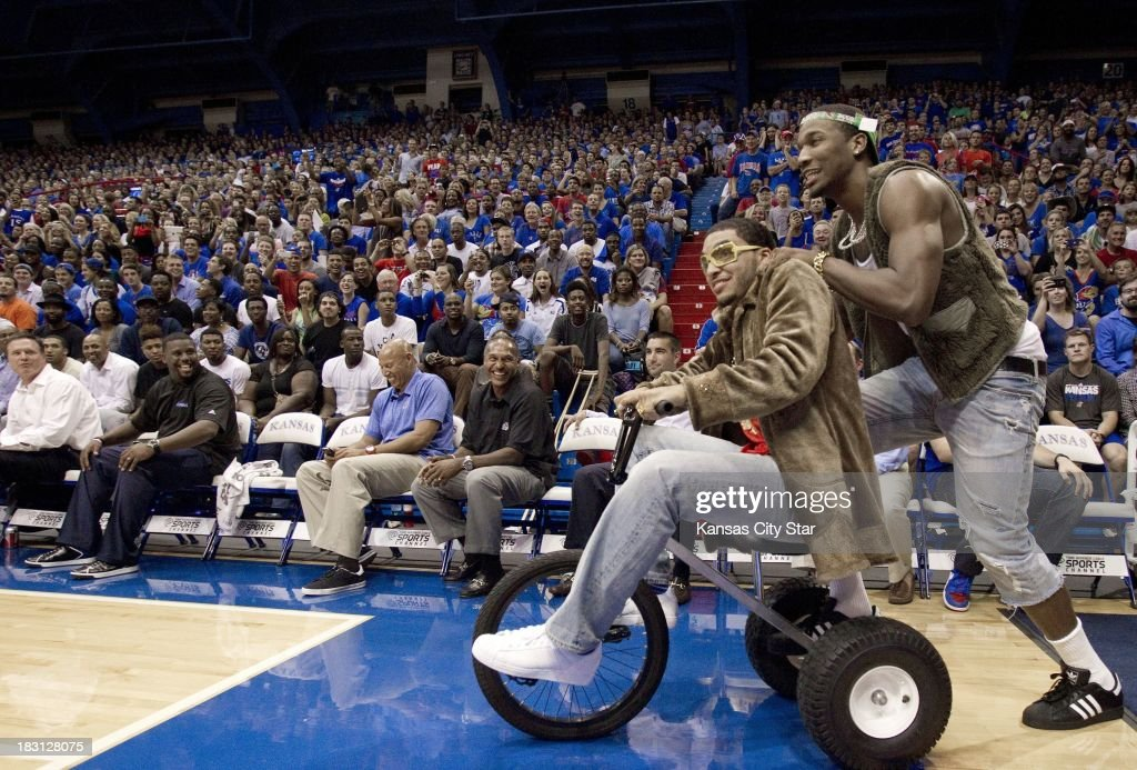 Kansas guard Niko Roberts (front) peddled a tricycle as Kansas guard Wayne Seldon, Jr., gave him a push, as they took the court for their skit during the University of Kansas Late Night at Phog Allen Fieldhouse in Lawrence, Kansas, Friday, October 4, 2013 in Lawrence, Kansas.