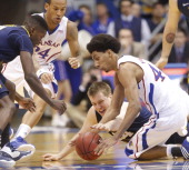 Kansas guard Travis Releford and forward Kevin Young dive for a loose ball with West Virginia center Aaric Murray in the first half at Allen...