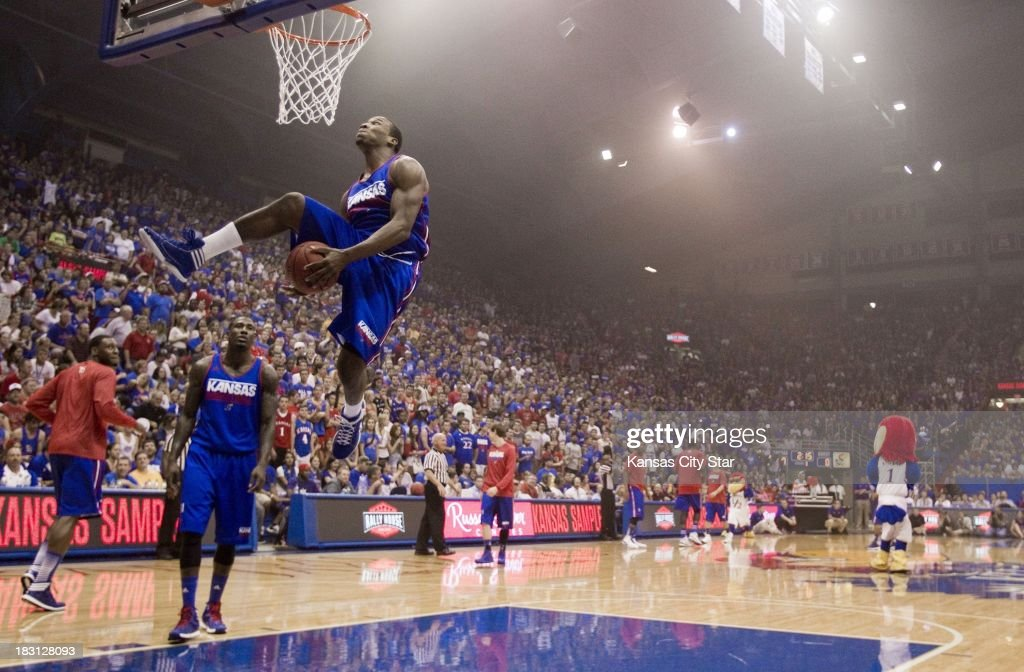 Kansas guard Wayne Seldon, Jr., passes the ball between his legs for a dunk while warming up for a scrimmage during the University of Kansas Late Night at Phog Allen Fieldhouse in Lawrence, Kansas, Friday, October 4, 2013.