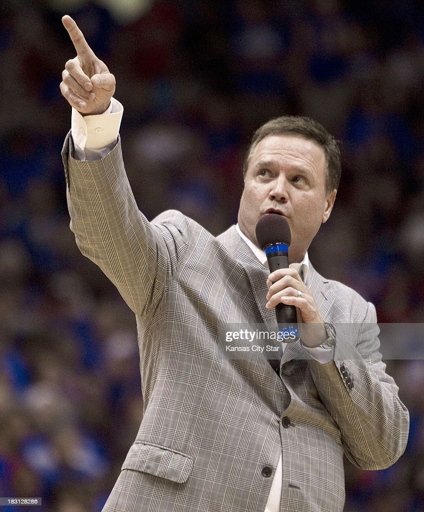 Kansas head coach Bill Self points to the rafters as he talks about adding another banner during the University of Kansas Late Night at Phog Allen Fieldhouse in Lawrence, Kansas, Friday, October 4, 2013.
