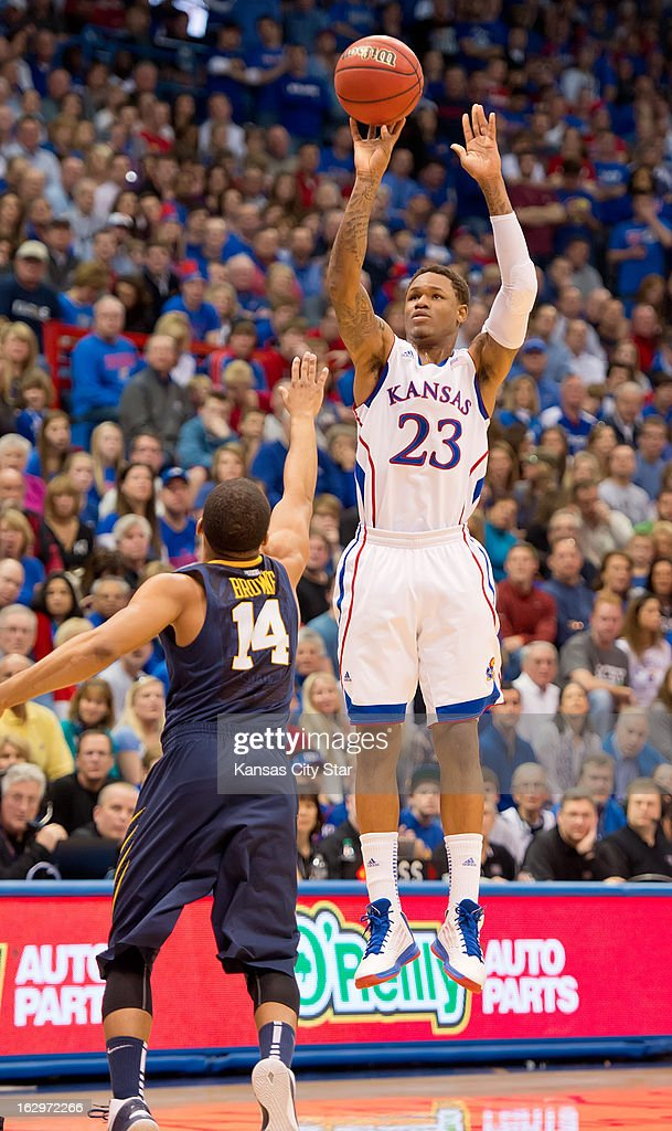 Kansas Jayhawks guard Ben McLemore (23) hits a three-point basket over West Virginia Mountaineers guard Gary Browne (14) in the first half at Allen Fieldhouse in Lawrence, Kansas, Saturday, March 2, 2013. Kansas defeated West Virginia, 91-65.