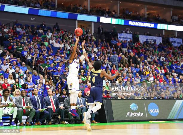 Kansas Jayhawks Guard Devonte' Graham takes a three point shot as UC Davis Aggies Guard Arell Hennings provides close out defense during the Kansas...