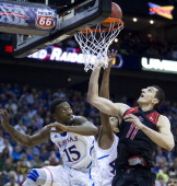 Kansas Jayhawks guard Elijah Johnson and Kansas Jayhawks forward Kevin Young tries to keep Texas Tech Red Raiders forward Dejan Kravic from scoring a...