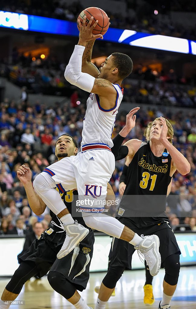Kansas Jayhawks guard Frank Mason III (0) drives to the basket around Wichita State Shockers guard Fred VanVleet (23) and guard <a gi-track='captionPersonalityLinkClicked' href=/galleries/search?phrase=Ron+Baker+-+Joueur+de+basketball&family=editorial&specificpeople=13909614 ng-click='$event.stopPropagation()'>Ron Baker</a> (31) during the first half of their third-round NCAA tournament game on Sunday, March 22, 2015, at CenturyLink Center in Omaha, Neb.