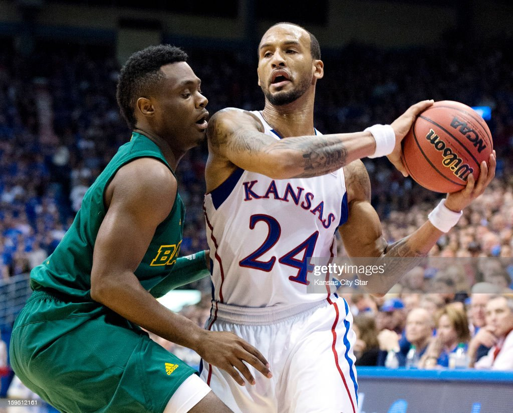 Kansas Jayhawks guard Travis Releford (24) keeps the ball away from Baylor Bears guard Gary Franklin (4) in the first half during Monday's basketball game on January 14, 2013, in Lawrence, Kansas.
