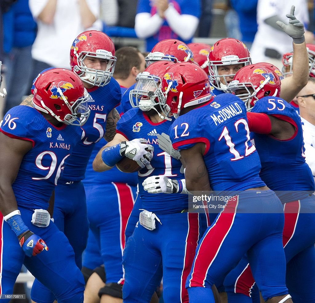 Kansas Jayhawks linebacker Ben Heeney (31) is surrounded by teammates after intercepting a pass during the first half against Texas Tech at Memorial Stadium in Lawrence, Kansas, Saturday, October 5, 2013. Texas Tech defeated Kansas, 56-16.