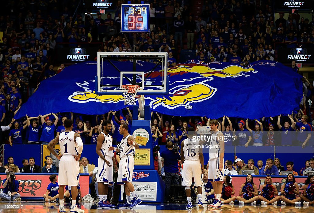 Kansas Jayhawks players walk onto the court as fans display a large banner during the game against the West Virginia Mountaineers at Allen Fieldhouse on March 2, 2013 in Lawrence, Kansas.