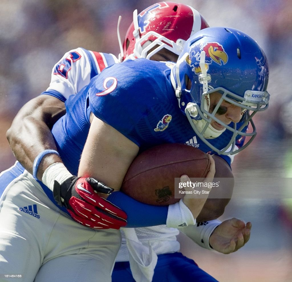 Kansas Jayhawks quarterback Jake Heaps (9) is tackled by Louisiana Tech Bulldogs linebacker Beau Fitte (6) during the first half at Memorial Stadium in Lawrence, Kansas, on Saturday, September 21, 2013. The Kansas Jayhawks defeated the Louisiana Tech Bulldogs, 13-10.