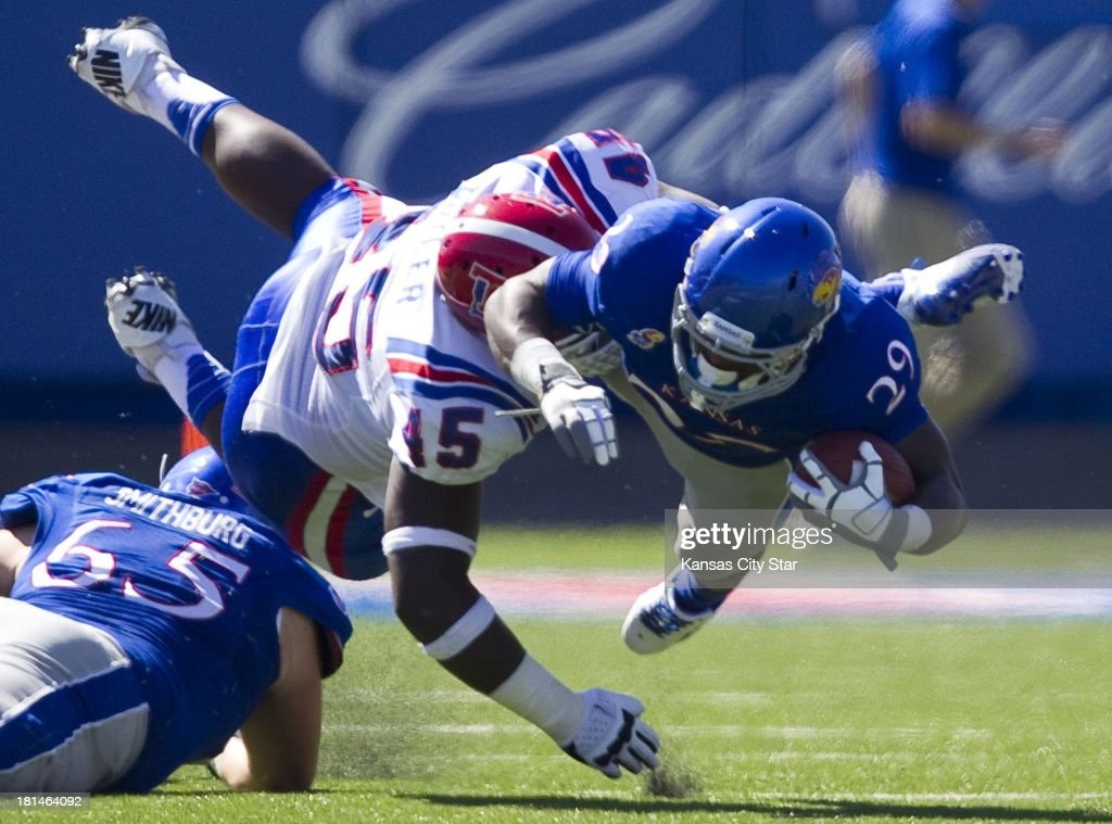 Kansas Jayhawks running back James Sims (29) dives for more yards as he was hit by Louisiana Tech Bulldogs defensive lineman Vernon Butler (45) during the first half at Memorial Stadium in Lawrence, Kansas, on Saturday, September 21, 2013. The Kansas Jayhawks defeated the Louisiana Tech Bulldogs, 13-10.