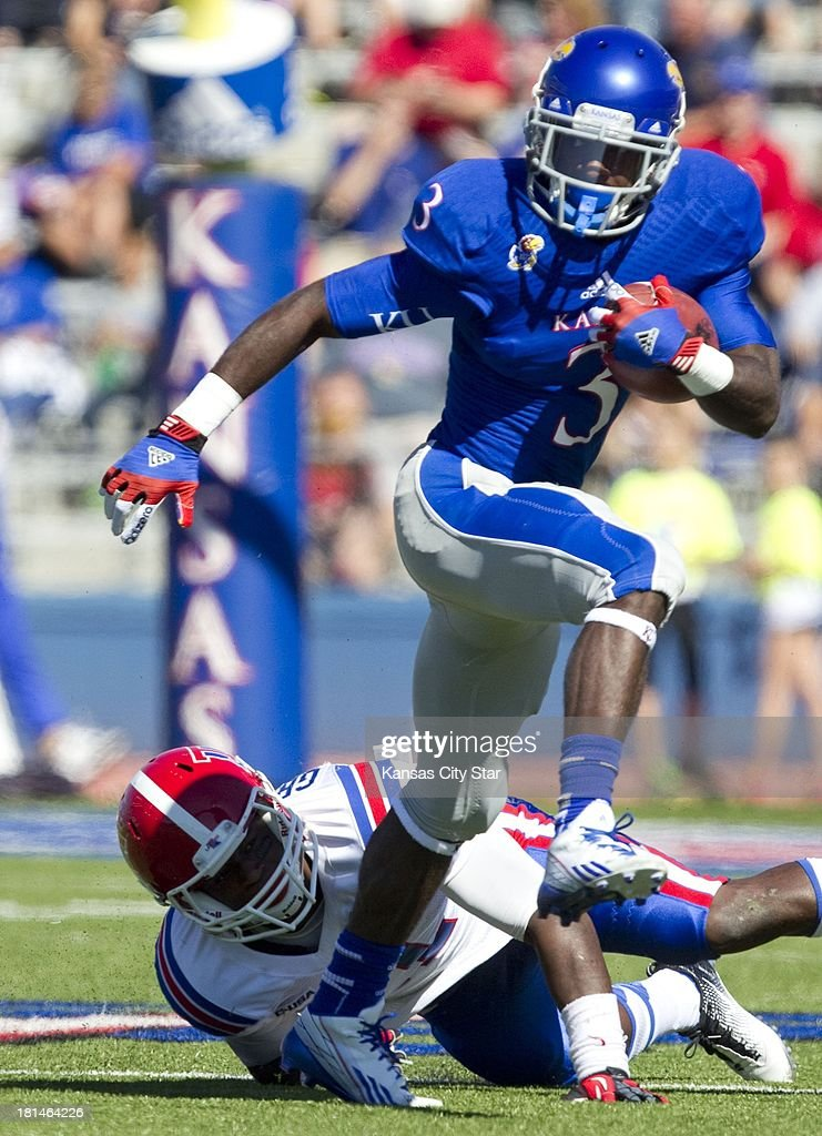 Kansas Jayhawks running back Tony Pierson (3) escapes the grasp of Louisiana Tech Bulldogs defensive back Lloyd Grogan (11) during the first half at Memorial Stadium in Lawrence, Kansas, on Saturday, September 21, 2013. The Kansas Jayhawks defeated the Louisiana Tech Bulldogs, 13-10.