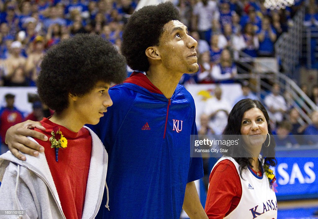 Kansas senior Kevin Young looks at the crowd as he was introduced during senior night at Allen Fieldhouse in Lawrence, Kansasm Monday, March 4, 2013. At left is his brother, Donovan, and to his right is his mother, Alicia Morales. Kansas defeated Texas Tech, 79-42.