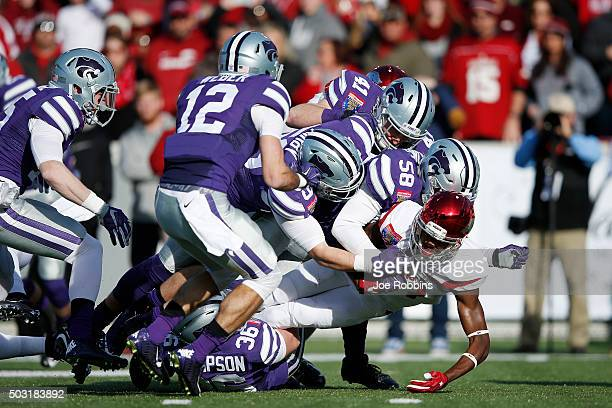 Kansas State Wildcats defenders converge to make a tackle for loss against Dominique Reed of the Arkansas Razorbacks in the first half of the...
