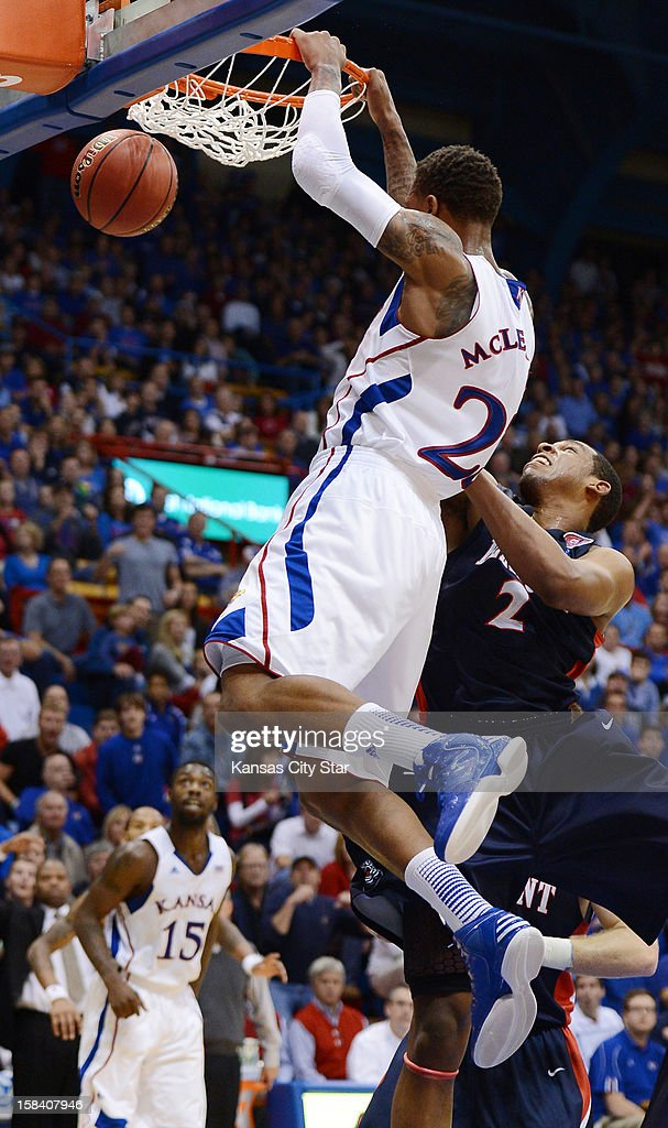 Kansas's Ben McLemore (23) completes an alley-oop dunk from a pass by teammate Elijah Johnson, rear, against Belmont's Blake Jenkins at Allen Fieldhouse in Lawrence, Kansas on Saturday, December 15, 2012.