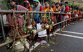 Kanwaria devotees hold pots of holy water and stand in the queue as they wait for their turn to pour holy water on the first Monday into the Shiva...