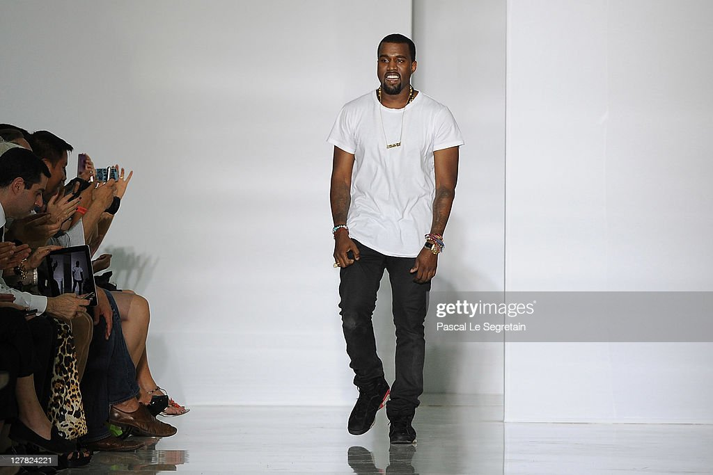Kanye West acknowledges the applause of the audience after the Dw by Kanye West Ready to Wear Spring / Summer 2012 show during Paris Fashion Week at Lycee Henri IV on October 1, 2011 in Paris, France.