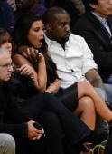 Kanye West puts his arm around Kim Kardashian from their courtside seats as the Los Angeles Lakers take on the Denver Nuggets in Game Seven of the...