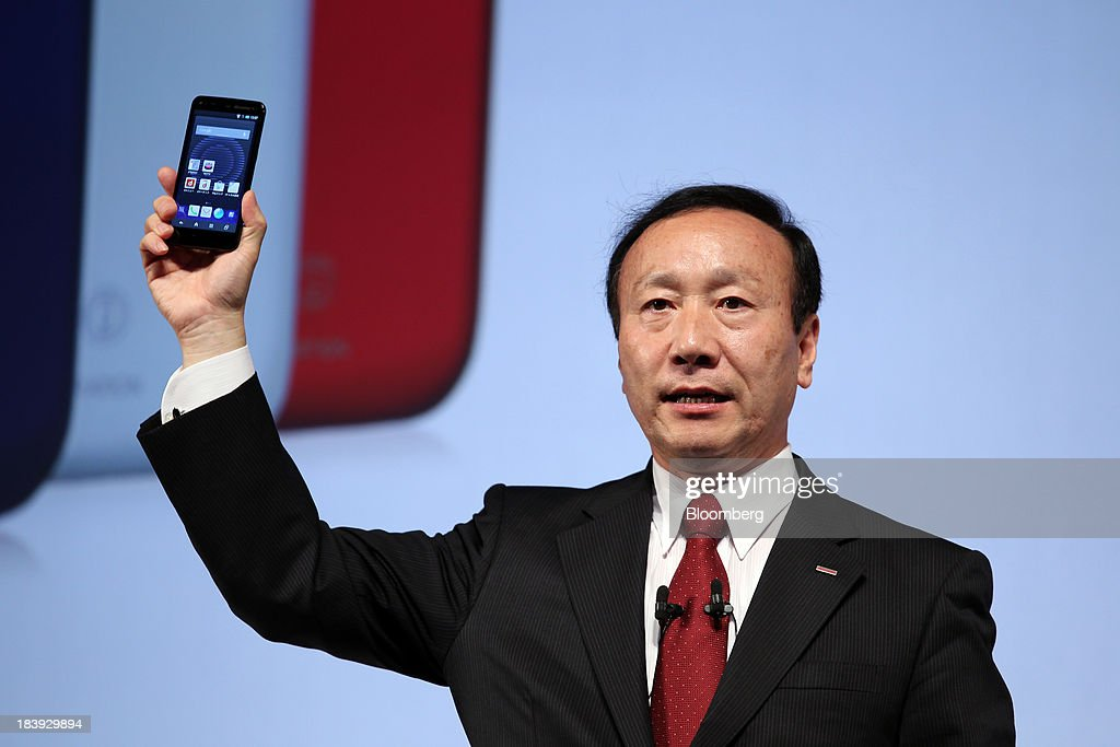 Kaoru Kato, president and chief executive officer of NTT DoCoMo Inc., holds a smartphone as he speaks during a news conference announcing the company's new smartphone models in Tokyo, Japan, on Thursday, Oct. 10, 2013. Kato said he is watching the price of mobile phones after SoftBank Corp. acquired Sprint Corp. Photographer: Junko Kimura/Bloomberg via Getty Images