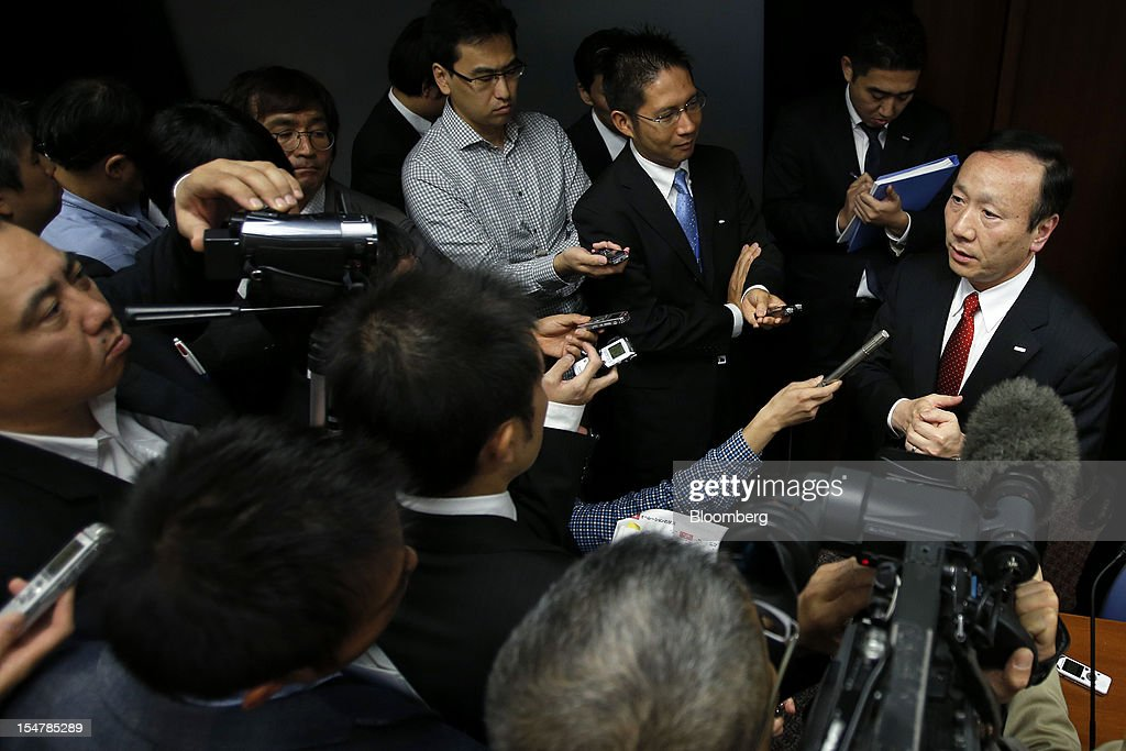 Kaoru Kato, president and chief executive officer of NTT DoCoMo Inc., right, speaks to the media after a news conference in Tokyo, Japan, on Friday, Oct. 26, 2012. NTT DoCoMo, Japan's largest mobile-phone company, cut its annual profit forecast 9 percent after competitors lured customers with Apple Inc.'s iPhone 5. Photographer: Kiyoshi Ota/Bloomberg via Getty Images