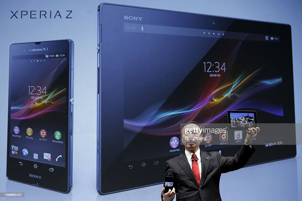 Kaoru Kato, president and chief executive officer of NTT DoCoMo Inc., holds up the company's Xperia Tablet Z SO-03E tablet computer, right, and Xperia Z SO-02E smartphone, manufactured by Sony Corp. as he speaks during a news conference in Tokyo, Japan, on Tuesday, Jan. 22, 2013. NTT DoCoMo, Japan's biggest mobile-phone company, released their latest tablet and smartphone series today. Photographer: Kiyoshi Ota/Bloomberg via Getty Images