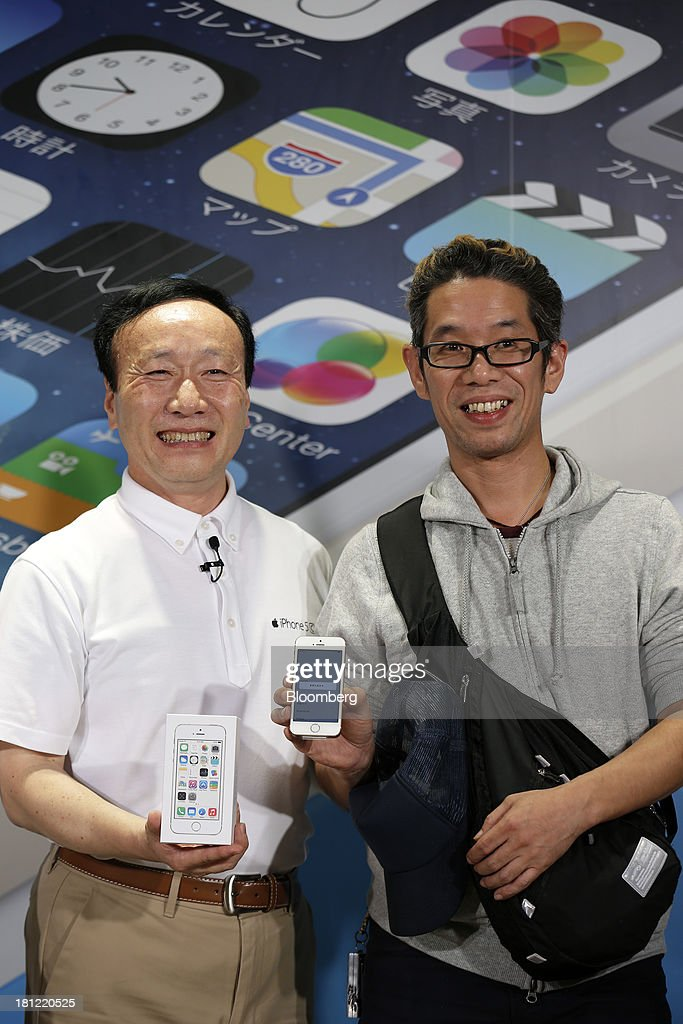 Kaoru Kato, president and chief executive officer of NTT DoCoMo Inc., left, poses with Hidenori Sato, the first customer to enter the company's store, as he holds the Apple Inc. iPhone 5S, during a launch event for Apple's new iPhones at an NTT Docomo Inc. store in Tokyo, Japan, on Friday, Sept. 20, 2013. Apple Inc. attracted long lines of consumers at its retail stores today for the debut of its latest iPhones, in the company's biggest move this year to stoke new growth. Photographer: Kiyoshi Ota/Bloomberg via Getty Images