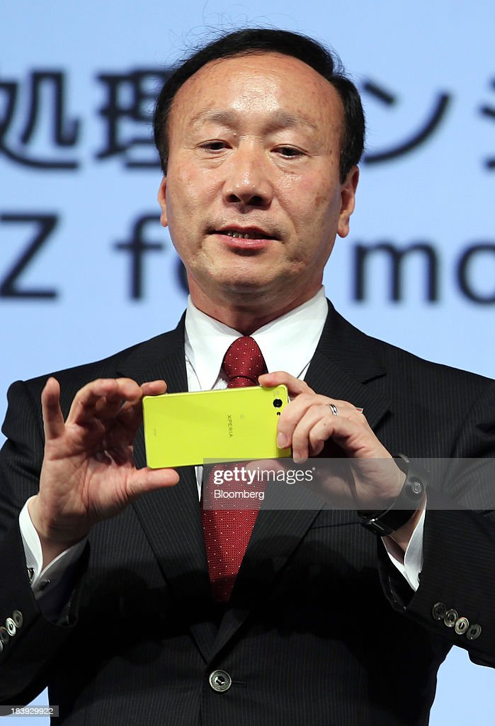 Kaoru Kato, president and chief executive officer of NTT DoCoMo Inc., holds an Xperia Z smartphone, manufactured by Sony Mobile Communications, as he speaks during a news conference announcing the company's new smartphone models in Tokyo, Japan, on Thursday, Oct. 10, 2013. Kato said he is watching the price of mobile phones after SoftBank Corp. acquired Sprint Corp. Photographer: Junko Kimura/Bloomberg via Getty Images