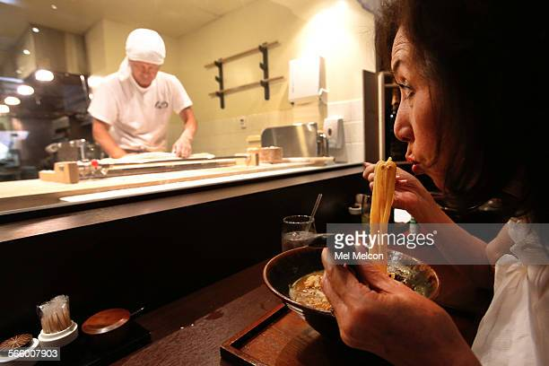 Kaoru Shimada visiting from Japan cools off her udon noodles while having lunch as Kenji Tateishi general manager at Monzo restaurant in Little Tokyo...