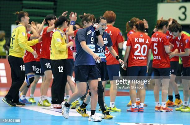 Kaoru Yokoshima and Mayuko Ishitate leaves the court while South Korean players celebrate qualified for the Rio de Janeiro Olympic after the handball...