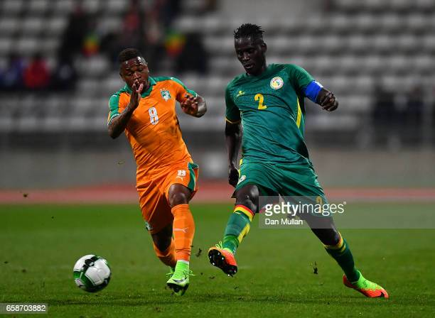 Kara Mbodj of Senegal holds off Cyriac Gohi Bi of the Ivory Coast during the International Friendly match between the Ivory Coast and Senegal at the...