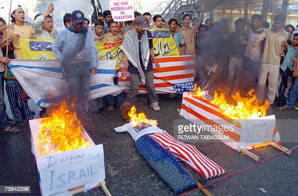 Pakistani Shiite students from the Imamia Students Organisation shout slogans infront of burning US and Israeli flag draped coffins and an effigy...