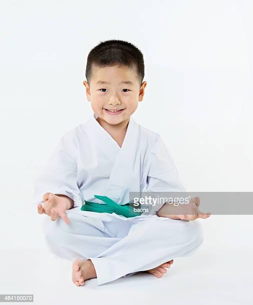 Karate boy sitting on floor