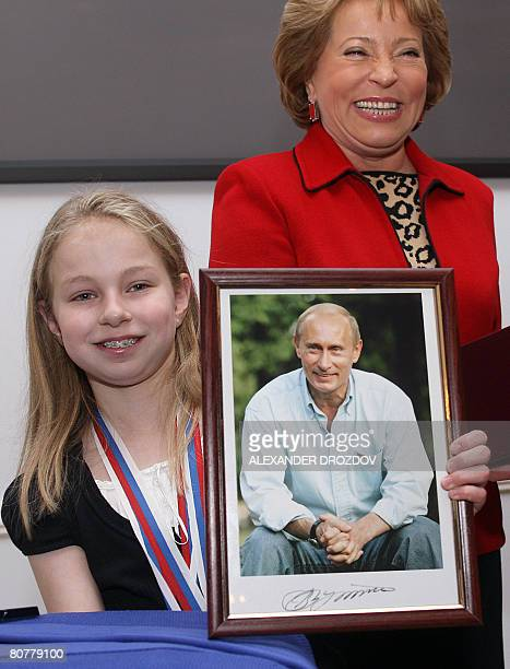 US karate fighter Samantha Smith from Pennsylvania poses holding a signed portrait of outgoing Russian President Vladimir Putin next to local...