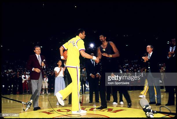 Kareem Abdul Jabbar shakes hands with Wilt Chamberlain before a ball game at the Los Angeles Forum in Los Angeles CA Chick Hearn the longtime Laker...