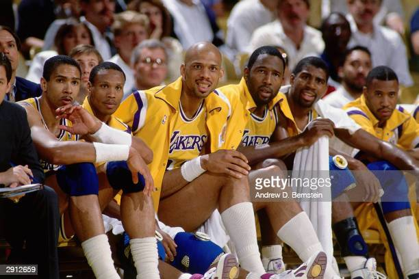 Kareem AbdulJabbar James Worthy and Magic Johnson of the Los Angeles Lakers watches the action from the bench with teammates during a game at The...