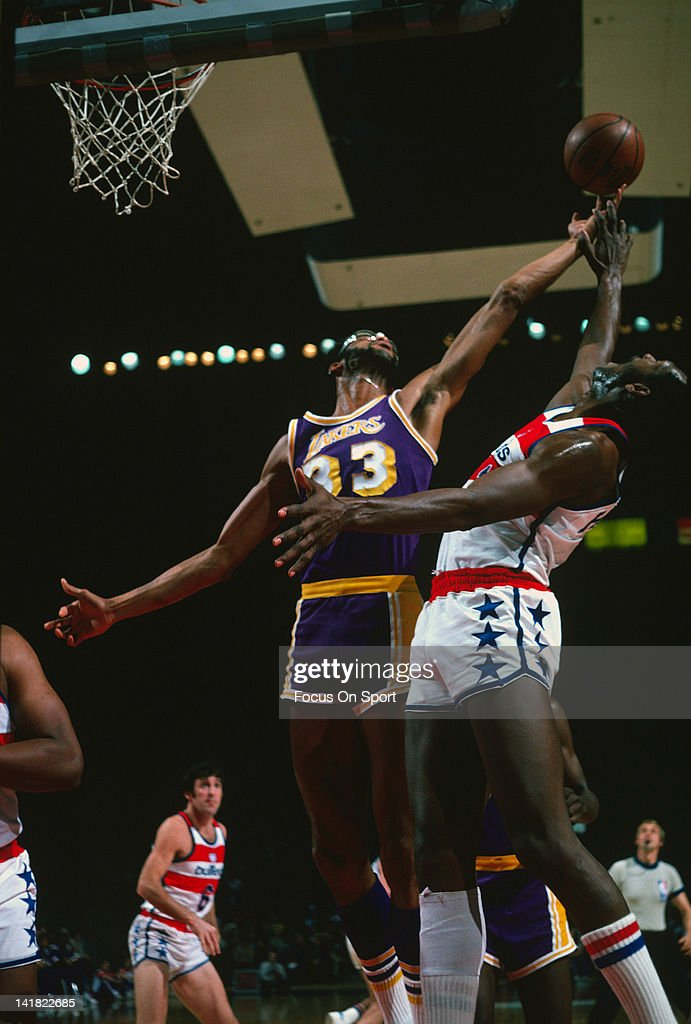 Kareem AbdulJabbar of the Los Angeles Lakers battles for a rebound with Elvin Hayes of the Washington Bullets during an NBA basketball game circa...