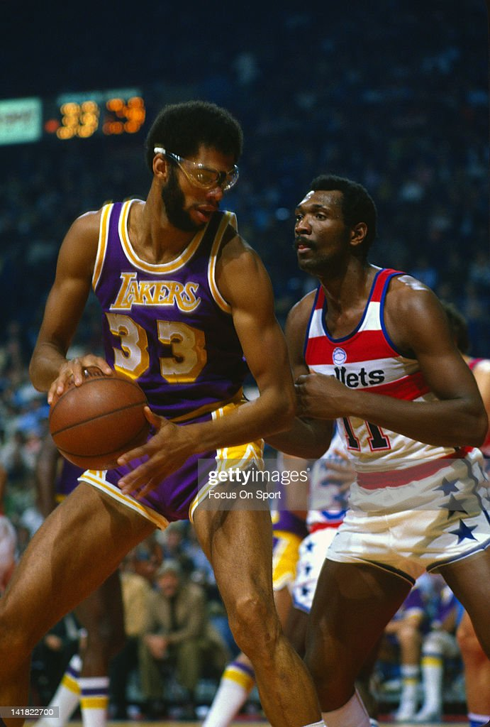 Kareem AbdulJabbar of the Los Angeles Lakers dribbles the ball backing in on Elvin Hayes of the Washington Bullets during an NBA basketball game...