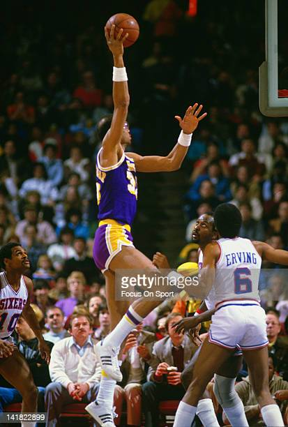 Kareem AbdulJabbar of the Los Angeles Lakers goes up to shoot over Moses Malone and Julius Erving of the Philadelphia 76ers during an NBA basketball...