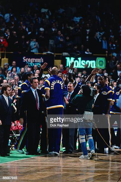 Kareem AbdulJabbar of the Los Angeles Lakers is greeted by teamates during a game played against the Boston Celtics in 1989 at the Boston Garden in...