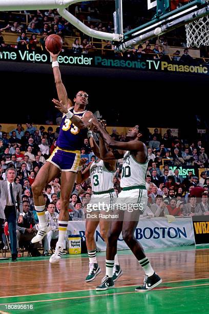 Kareem AbdulJabbar of the Los Angeles Lakers shoots a skyhook over Dennis Johnson and Robert Parish of the Boston Celtics during a game circa 1984 at...