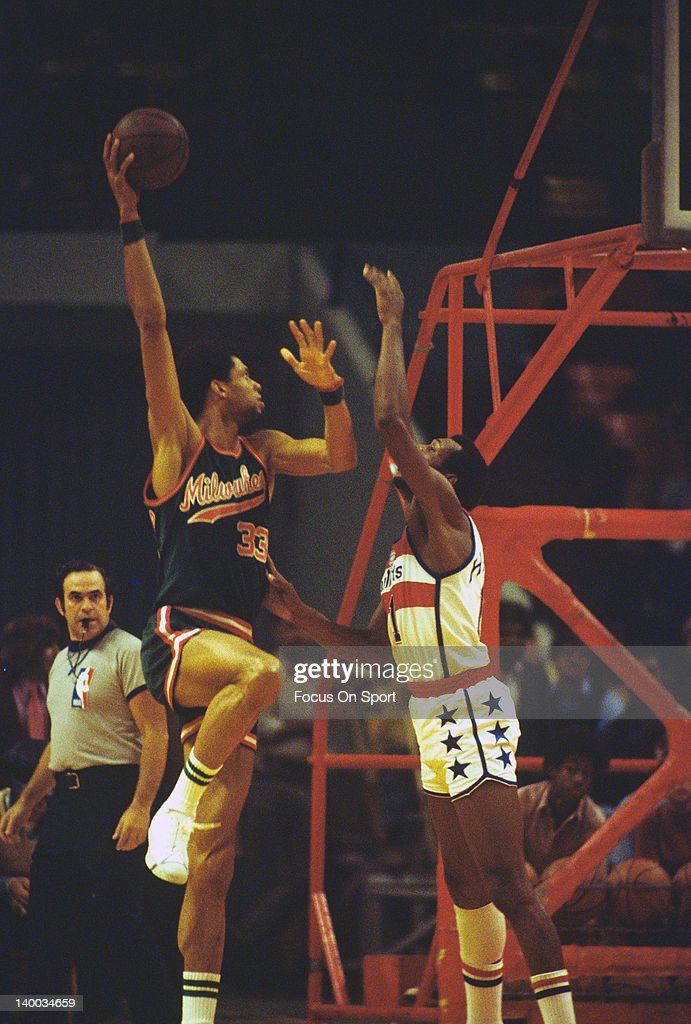 Kareem AbdulJabbar of the Milwaukee Bucks shoots a hook shot over Elvin Hayes of the Washington Bullets during an NBA basketball game circa 1975 at...