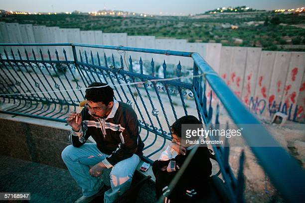 Kareem Abu Aker smokes a cigarette along side his son Mohammed on their balcony inside the Aida refugee camp overlooking the concrete separation...