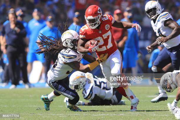 Kareem Hunt of the Kansas City Chiefs avoids the tackle against Tre Boston of the Los Angeles Chargers during the NFL game at the StubHub Center on...
