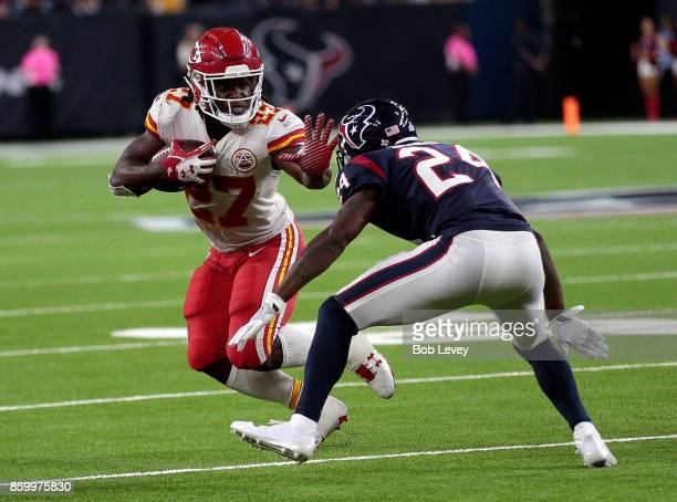 Kareem Hunt of the Kansas City Chiefs extends his arm toward Johnathan Joseph of the Houston Texans as he rushes in the fourth quarter at NRG Stadium...