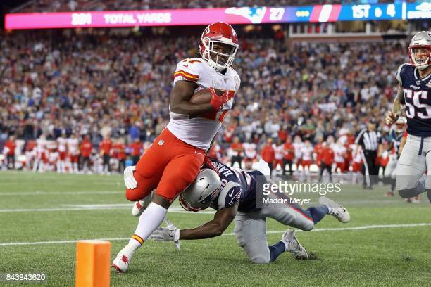Kareem Hunt of the Kansas City Chiefs runs for a 4yard rushing touchdown as Duron Harmon of the New England Patriots attempts to tackle him during...