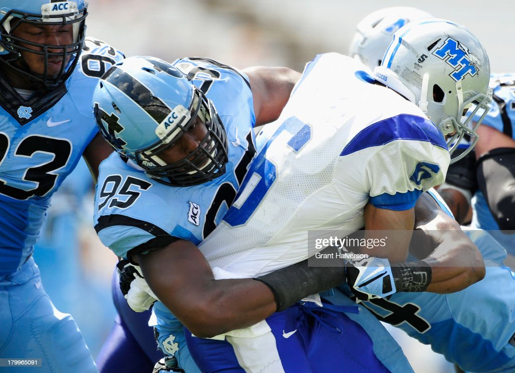Kareem Martin #95 of the North Carolina Tar Heels tackles Jordan Parker #6 of the Middle Tennessee State Blue Raiders during play at Kenan Stadium on September 7, 2013 in Chapel Hill, North Carolina. North Carolina won 40-20.