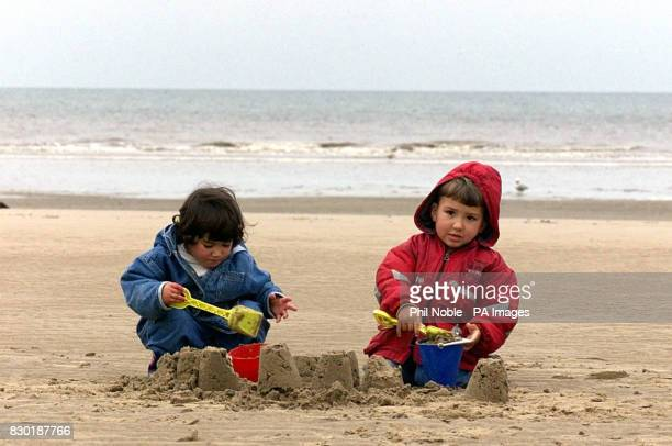Kareen and her old brother Yousuff brave the cold weather to build sandcastles on a deserted beach at Blackpool as temperatures in the north of...